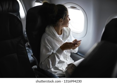 Glad girl is looking into the window while sitting in the airplane and holding a cellphone in a pink case. She wears a white hoodie and has a light backpack. Horizontal.