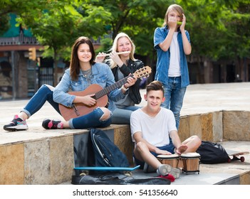 Glad girls and boys teenagers friends with musical instruments together outdoors