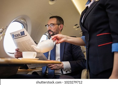 Glad groomed businessman reading newspaper in airplane while stewardess is serving tea