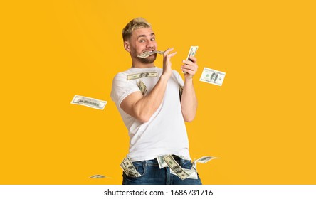 Glad guy holds banknote in his teeth and scatter money, panorama