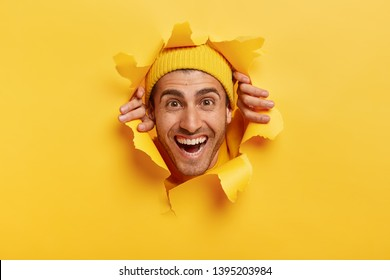 Glad handsome man with toothy smile, joyful expression, tears paper wall, feels glad to see something in front, wears yellow headgear, has bristle. Positive human emotions and feelings concept