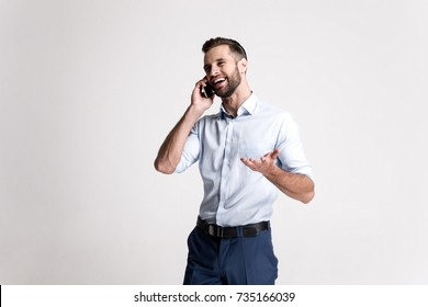 So glad to hear you! Handsome young man using his phone with smile while standing against white background.