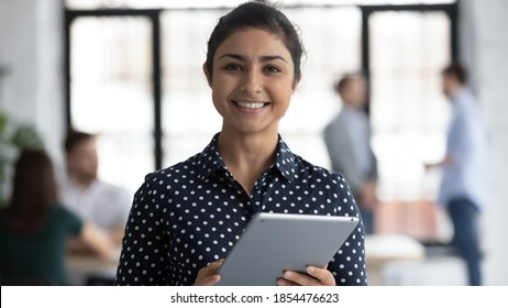 Glad to help you! Portrait of smiling confident indian female insurance broker bank manager hr assistant standing in open space office holding digital tablet looking at camera ready to assist client