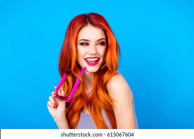 Glad joyful carefree girl with beautiful red curly long hair holding sunglasses and look to the side while standing on blue background