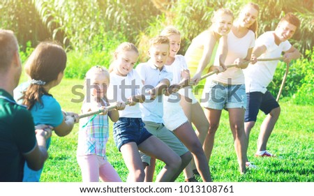 Glad Kids With Moms And Dads Playing Tug Of War During Joint Outdoors Games On Sunny