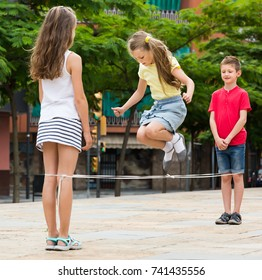 Glad kids in school age playing together with chinese jumping rope outdoors