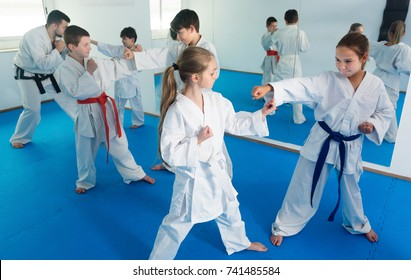 Glad kids sparring in pairs to practice new moves in karate class
