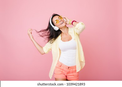 Glad latin woman with black hair waving dancing and dreaming about something. Cheerful woman in colorful accessories enjoying music and smiling to camera. Place for text.