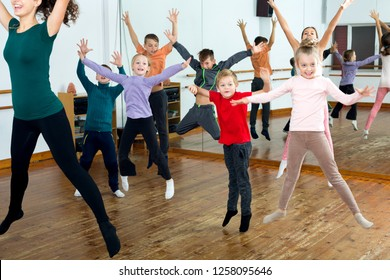 Glad little children studying modern style dance in class