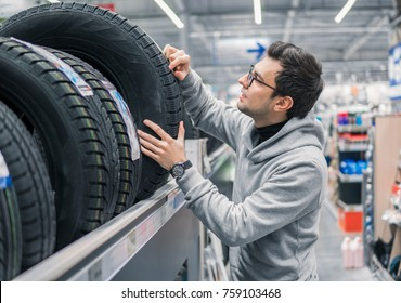 Glad male customer taking new tires in the supermarket for buying. He looks happy. Big shopping mall with car goods.