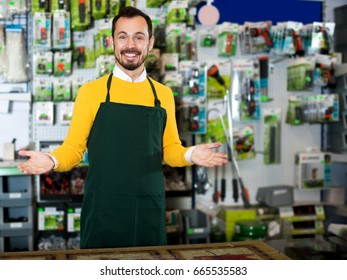 Glad male seller displaying various items in garden equipment shop