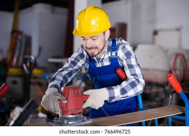 Glad male worker starting to work with instrument at workshop