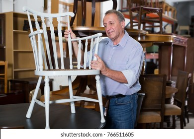 Glad man is shopping the old furniture in the antique store