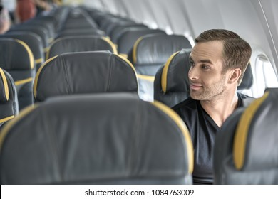 Glad man sits in the airplane next to the window on the background of the empty seats and other passengers. He wears a black T-shirt and looks to the side with a smile. Closeup. Horizontal.
