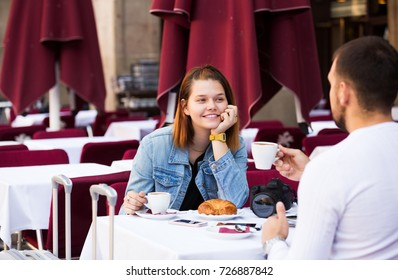 Glad man and woman sitting with coffee and talking at the table in street cafe
