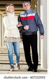 Glad mature couple goes for walk between concrete pillars on sunny day