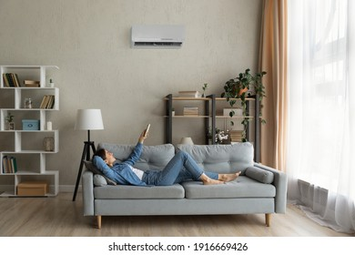 Glad millennial female buyer of air conditioner relax on sofa hold controller breath cool fresh air despite of hot summer day outside. Happy young lady regulate climate at home using modern ac device