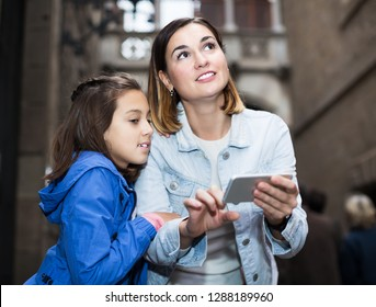 Glad mother and daughter reading guide in phone during sightseeing tour
