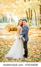 Glad newlyweds stand on fallen leaves in autumn park