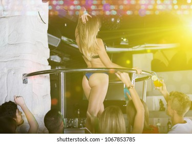 Glad nice woman dancer gogo dancing in the night club on stage