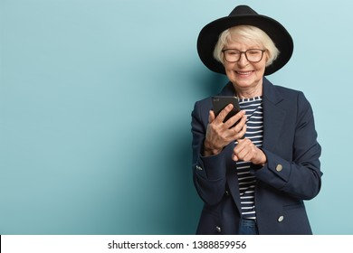 Glad old woman receives good news on smart phone, types feedback, wears fashionable black hat, jacket and striped jumper, happy to learn using modern technologies, stands indoor over blue wall