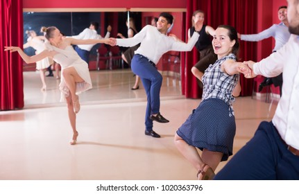 Glad partners dancing lindy hop in dance hall