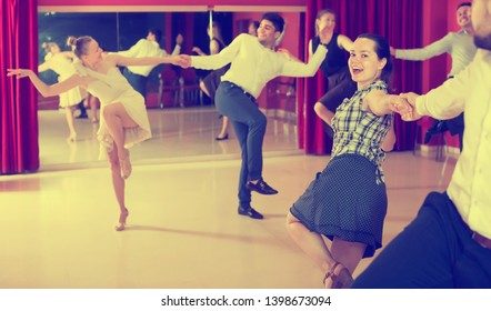 Glad partners dancing lindy hop in dance hall