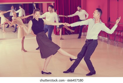 Glad people dancing lindy hop in pairs in dance hall