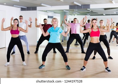 Glad people of different ages studying zumba dance elements in dancing class