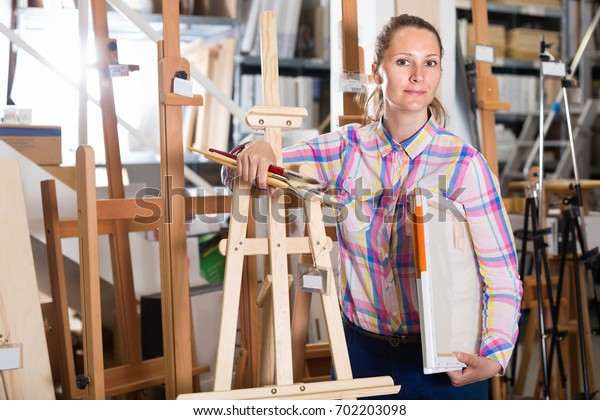 Glad pleasant smiling woman shopping various supplies in art store