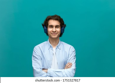 I am glad. Portrait of a young beautiful man wearing white t-shirt and blue shirt with headphones fold ones arms and looking at camera