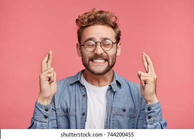 Glad positive bearded man crosses fingers, closes eyes with pleasure, anticipate hearing good news, isolated pink background. Happy male rejoices that his dreams came true. Excitement concept