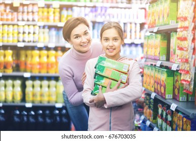 Glad positive female shopper with teenage daughter searching for beverages in supermarket