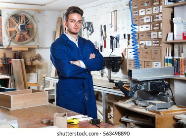 Glad  positive guy displaying his workplace and tools at workshop