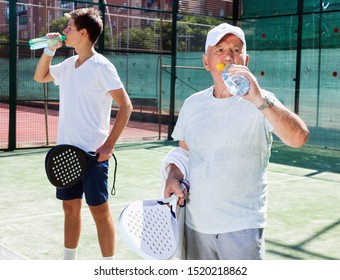 Glad positive padel players of different generations drink water on padel court