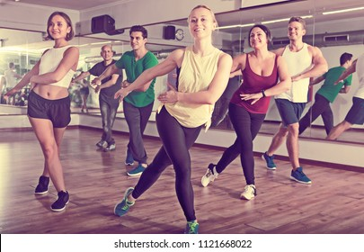 Glad positive people learning zumba steps in dance hall