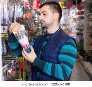 Glad  positive smiling man customer choosing fishing lures near stand in the sports shop