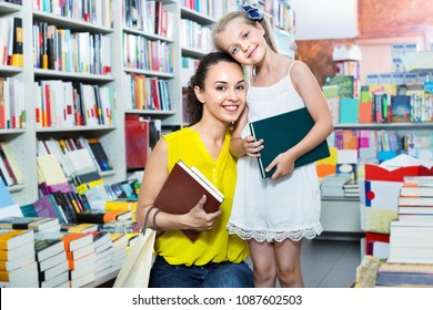 Glad positive woman with cute small girl taking literature books in store with prints