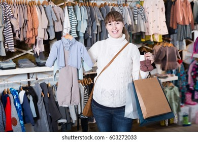 Glad pregnant mother choosing clothes for baby in childrenâ??s cloths shop