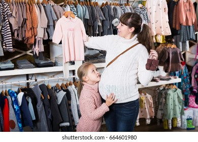 Glad pregnant mother and daughter choosing romper suits for baby in childrens cloths shop