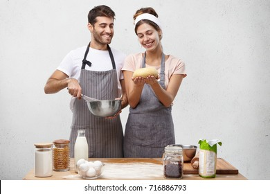 Glad pretty housewife show well made dough to husband, feel proud of cooking mastery. Affectionate husband helps wife with baking doughnut, mix eggs in bowl. Teamwork, baking and cooking concept