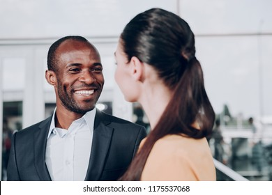 Glad to see you. Close up portrait of two people smiling. Focus on man in jacket looking genuinely at girl standing back to the camera