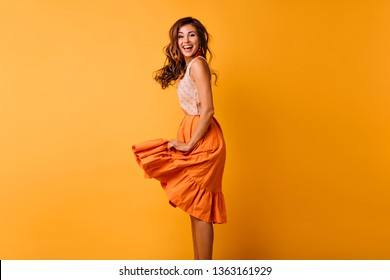 Glad slim girl in orange skirt expressing good emotions. Studio photo of ecstatic curly woman in summer attire.