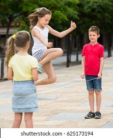 Glad small kids in school age playing together with chinese jumping rope outdoors. Focus on boy