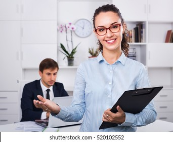 Glad smiling efficient business female secretary having cardboard in hands and working in office