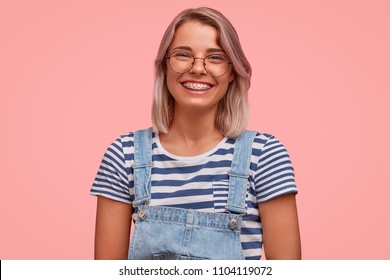Glad smiling pretty female freelancer, has broad smile, demonstrates teeth with braces, wears casual t shirt with overalls, rejoices recieving reward, stands against pink background. Emotions concept