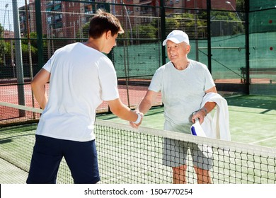 Glad smiling senior and young man shake hands before padel tennis match