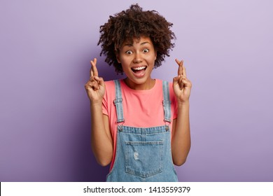 Glad smiling woman wishes luck, feels thrilled emotions, keeps fingers crossed, dreams about getting promotion, hopes for something desirable, isolated over purple background. People and wish