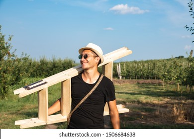 Glad smiling young man gardener in white hat, black t-shirt and sunglasses walking among his gardens with stepladder on his shoulder and looking at left side, sunny summer day, farmer lifstyle concept