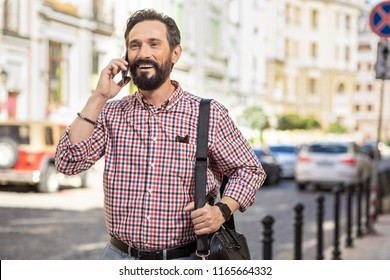 Glad to talk to you. Waist up of a cheerful delighted man talking on phone while walking along the street